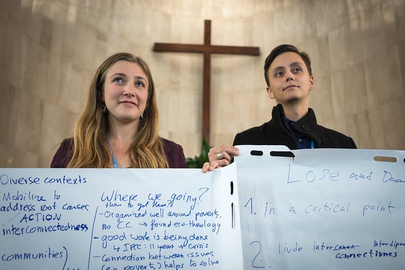 1 December 2019, Madrid, Spain: Lutheran World Federation delegates Erik Bohm from Church of Sweden (right) and Erika Rodning from the Evangelical Lutheran Church in Canada (left) hold sheets of paper on which key discussion points have been summarized, as representatives of various faiths gather in the Iglesa de Jesús (Church of Christ) of the Iglesia Evangélica Española (Evangelical Church of Spain) for an interfaith dialogue and prayer service on the eve of the United Nations climate conference (COP25) in Madrid, Spain.